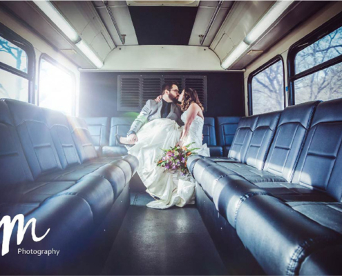 Bride and groom sit at the back of a Voigt bus and kiss while sunlight streams in