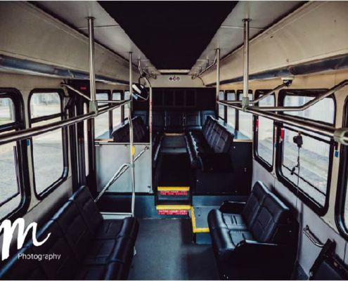 Interior of a Voigt bus featuring plush black seats with an upper section of seats elevated about a foot