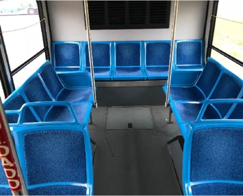Blue seats arranged in a U shape on a chartered Voigt bus