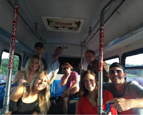 Group of eight young people taking a group picture aboard a Voigt's bus
