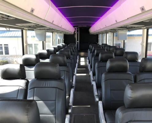 Wide shot of the interior of a Voigt bus. Seats are all black and lighting is purple