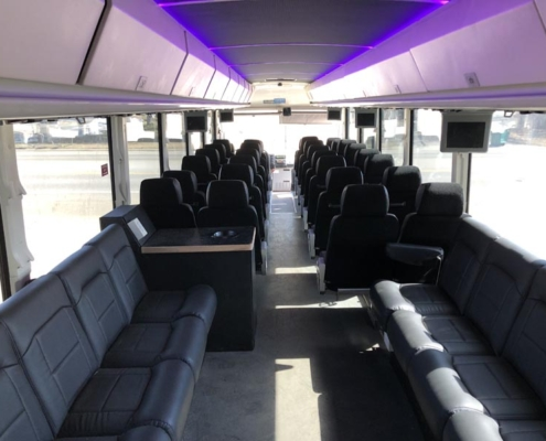 Wide shot of the interior of a signature Voigt bus. Seats are all black and lighting is purple