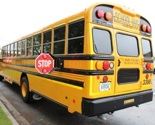 Backview of school bus parked in front of school building