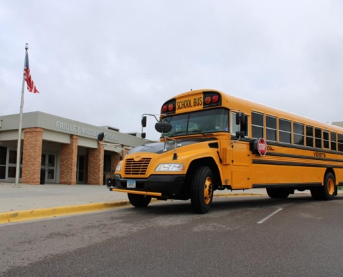 Side view of yellow school bus parked in front of school building