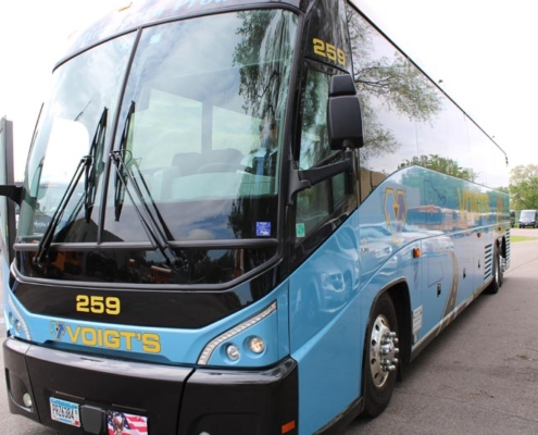 Front view of a light blue Voigt bus featuring a loon, Minnesota state outline, and other Minnesota elements