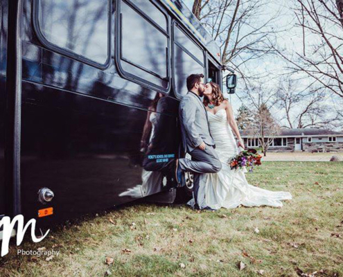 Bride and groom lean against the side of a Voigt bus and share a kiss