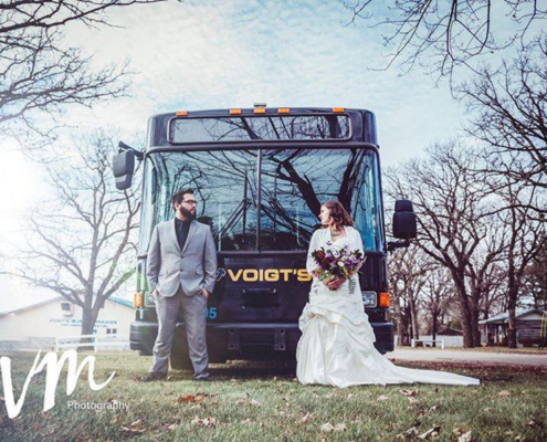 Couple in wedding attire standing in front of a Voigt bus on a cool day