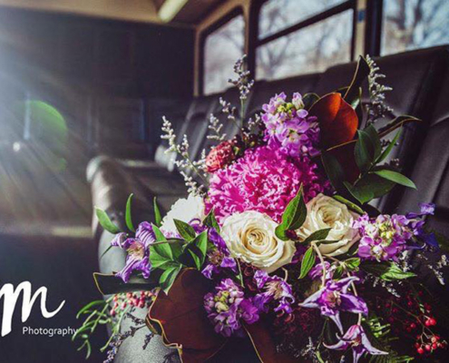 Bright pink, white, and purple wedding bouquet lying on the black seat of a Voigt bus as sunlight shines in